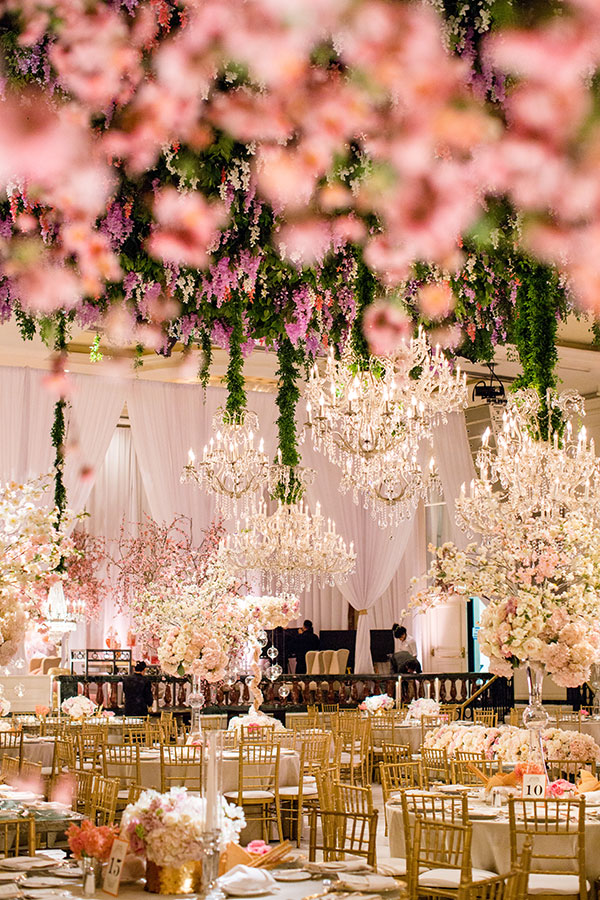 A real life fairytale, this ceiling has been adorned with masses of greenery and wisteria, offset by a collection of sparkling chandeliers. Photography: Samuel Lippke Studios