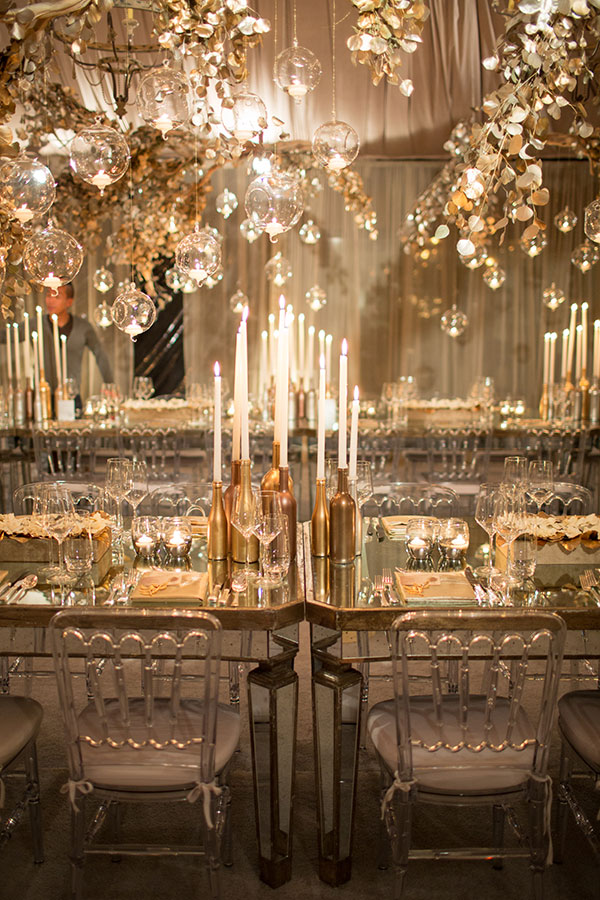 Sprayed gold branches dripping with tea light-filled baubles create a heavenly marquee ceiling. Photography: Samuel Lippke Studios