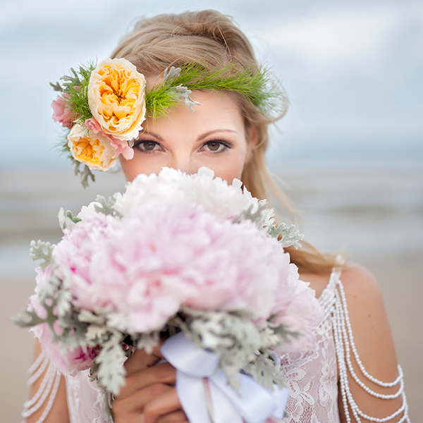 Bride holding flowers on beach