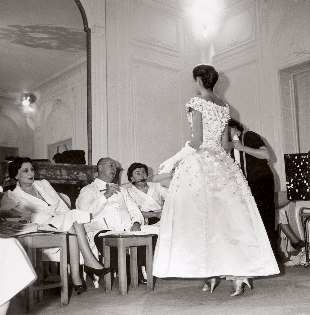 Christian Dior working with Mitzah Bricard (left) and Marguerite Carré (right) on the Première soirée dress, autumn−winter 1955 haute couture collection © Christian Dior Photo: Bellini