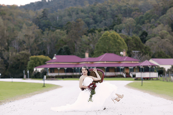 Hinterland wedding: Bride sitting on a chair outside O'Reilly's Canungra Valley Vineyards