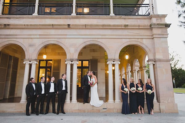 Bride and groom kissing on the steps of Old Government House with the bridal party watching on