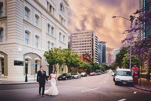 Bride and groom walking across the street.