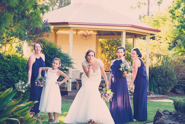 Bride, bridesmaids and flowergirl posing for a photo.
