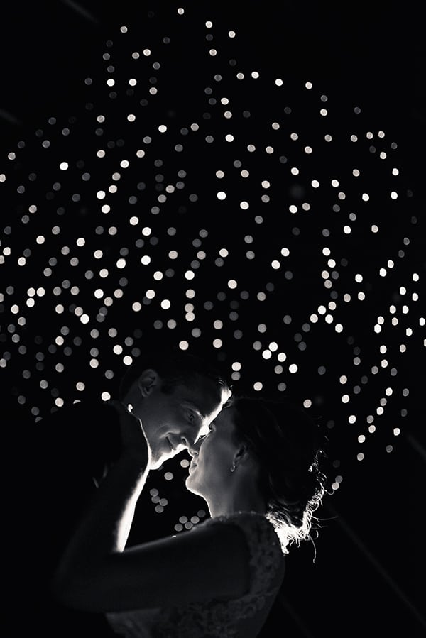 Brie and groom dancing under the night sky.