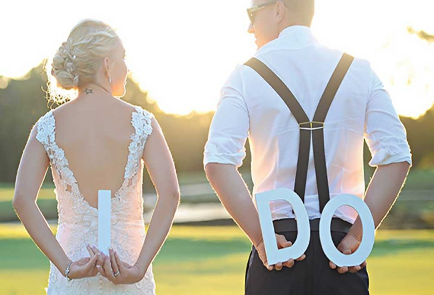 "Bride and groom with ""I DO"" letters."