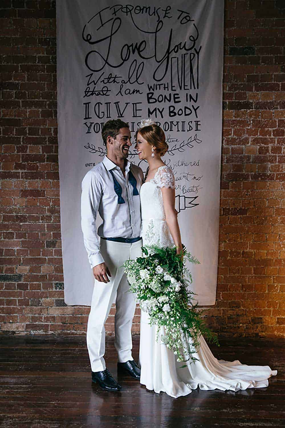 A bride and groom with a cascading bouquet.