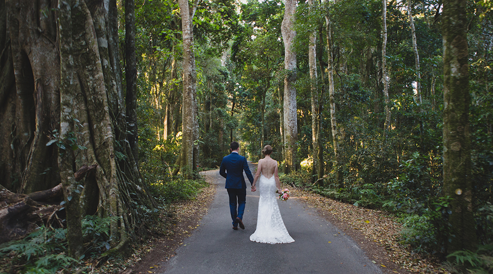 Bride and groom walking through the forest for their gold coast hinterland wedding