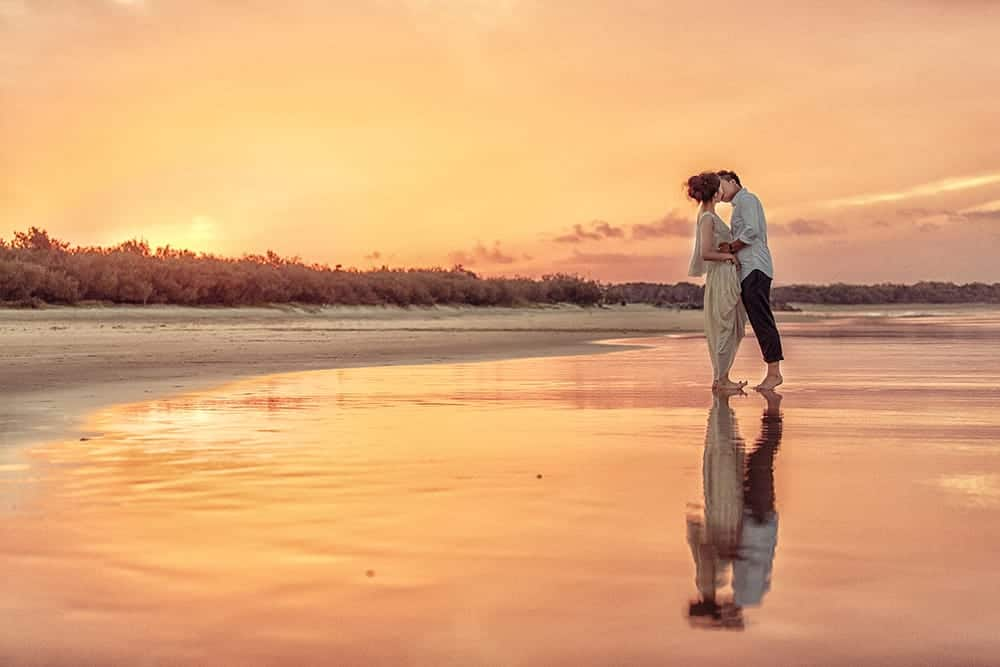 Bride and groom kissing on the beach at sunset.