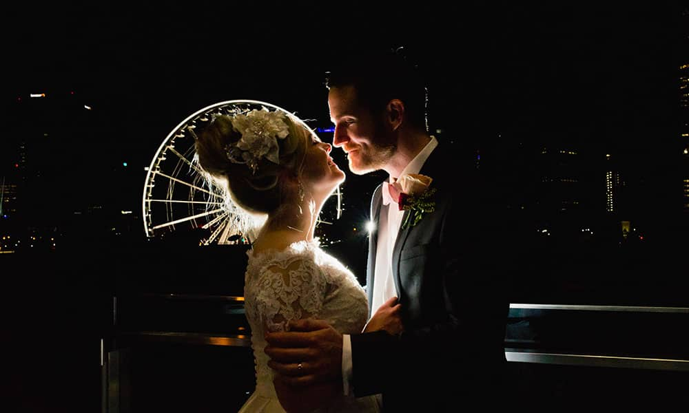 Riverside receptions: Bride and groom with the Brisbane Eye in the background for their wedding at Skyroom & Terrace.