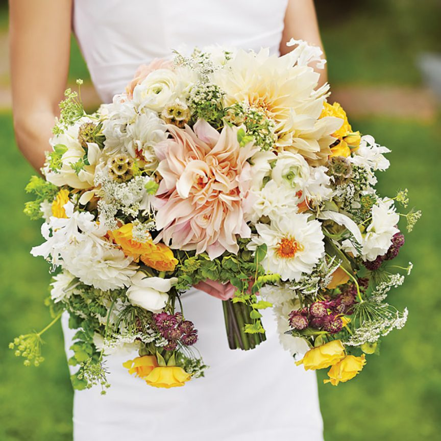 Cascading bouquet with orange, white and pink hued florals.