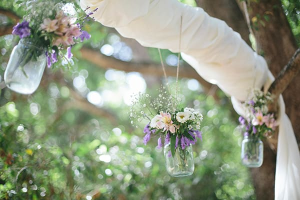 hanging jars with flowers at a country wedding