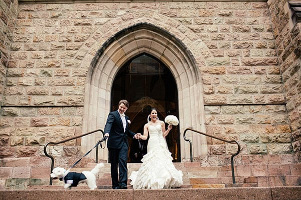 Bride and groom leaving the church with their tuxedo-dressed pooch.