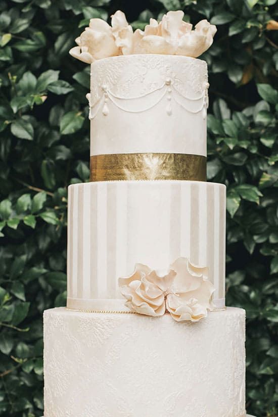 white wedding cake with gold foil belt