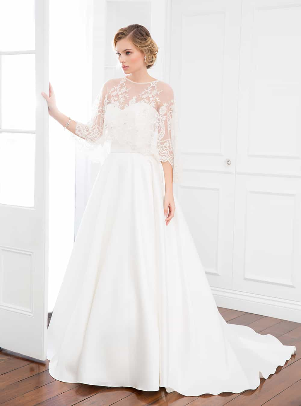 The Carolyn wedding gown with white sheer laced cape from Wendy Makin Couture.