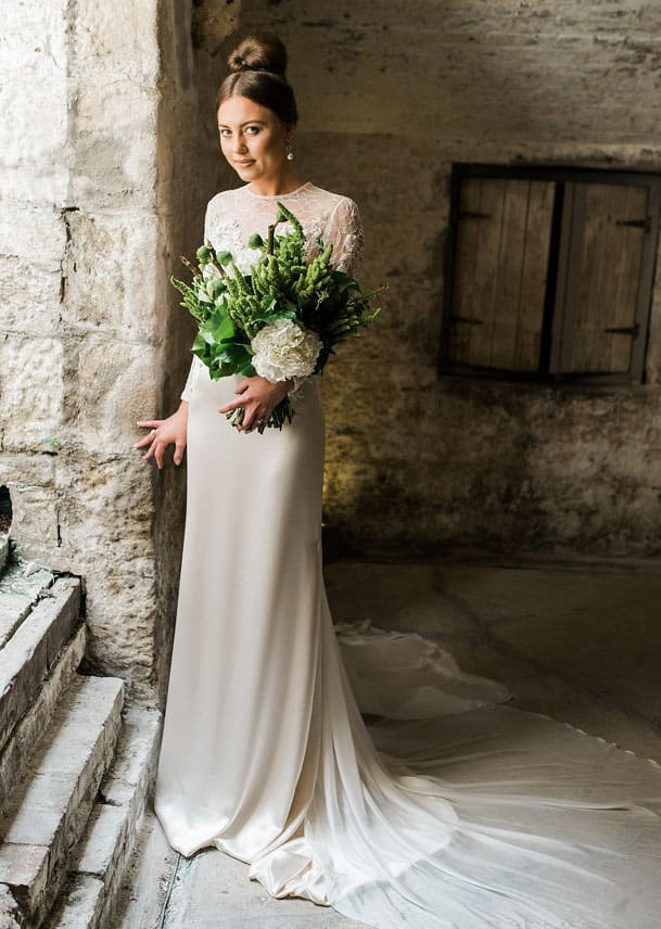 Bride wearing long sleeve lace with train wedding gown holding succulent bouquet.