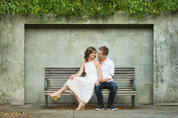 Engagement photo session of couple sitting at a street bench.