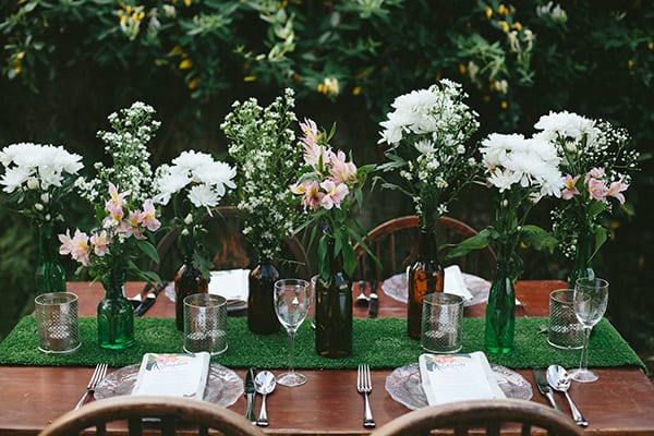 centrepieces featuring beer bottles as vases at a country wedding