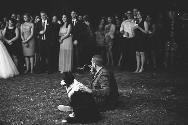 Pets at weddings: Photographer sitting with dog at a wedding.