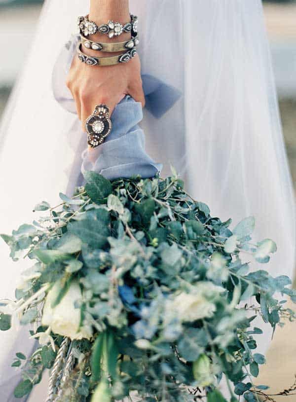 Bride holding a leafy green bouquet with white roses