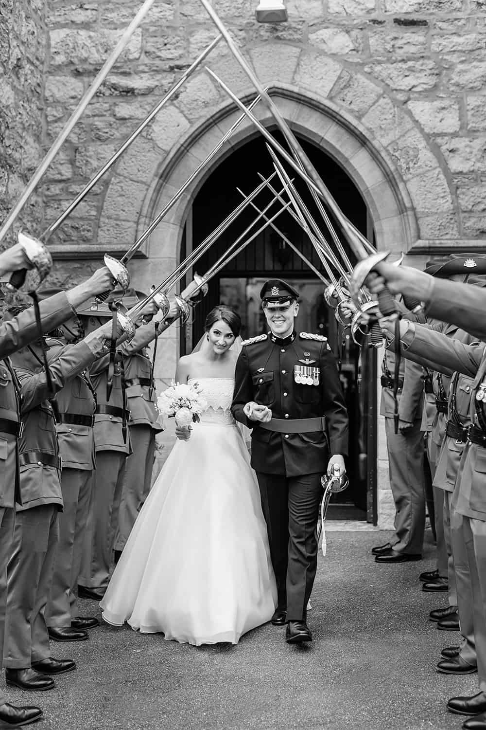 Just married - Real bride Lucy and her husband walking under a guard of honour.
