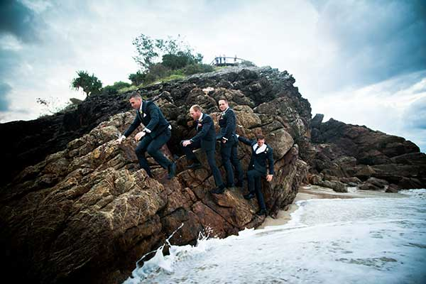 Groom and groomsmen on the beach for a winter beach wedding.