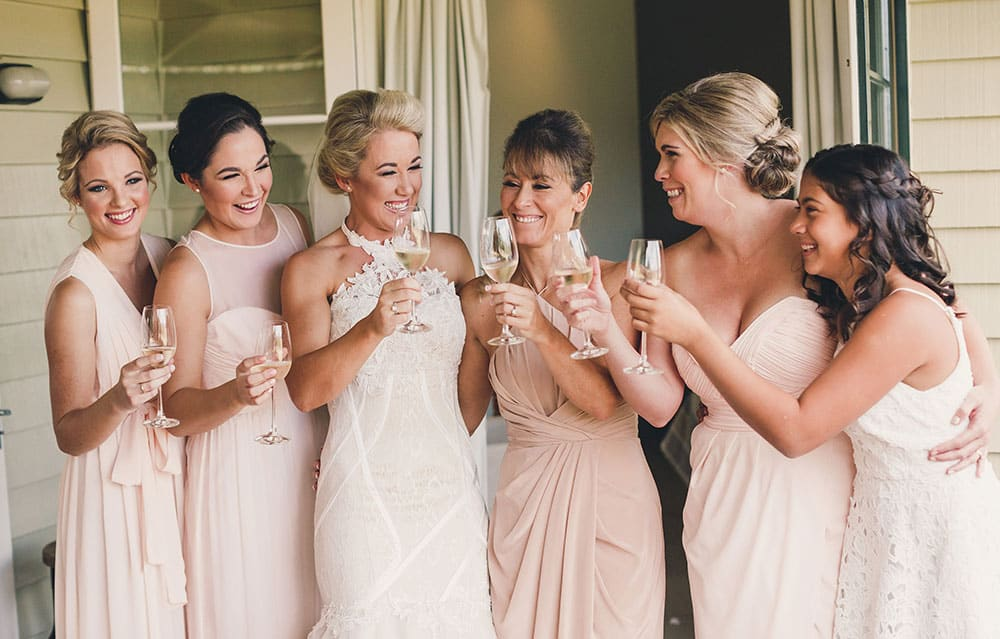 Blush pink bridesmaid dresses in different shapes and cuts.