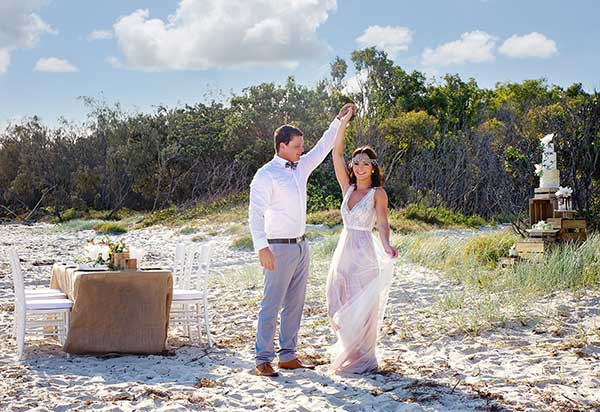 boho bride and groom having a dance at their coastal-style wedding