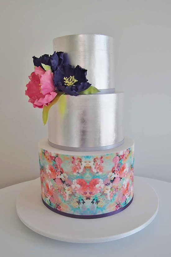 silver foil wedding cake with pink and blue flowers