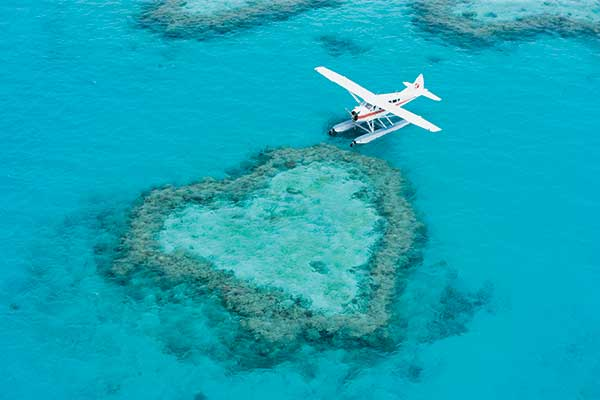 Sea plane over green island, just a quick trip from Airlie Beach