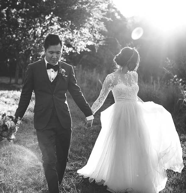 Bride and groom walking through a paddock by Jess Marks Photography.