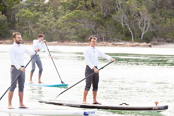 Groom + groomsmen arriving in style on a stand-up paddle board.