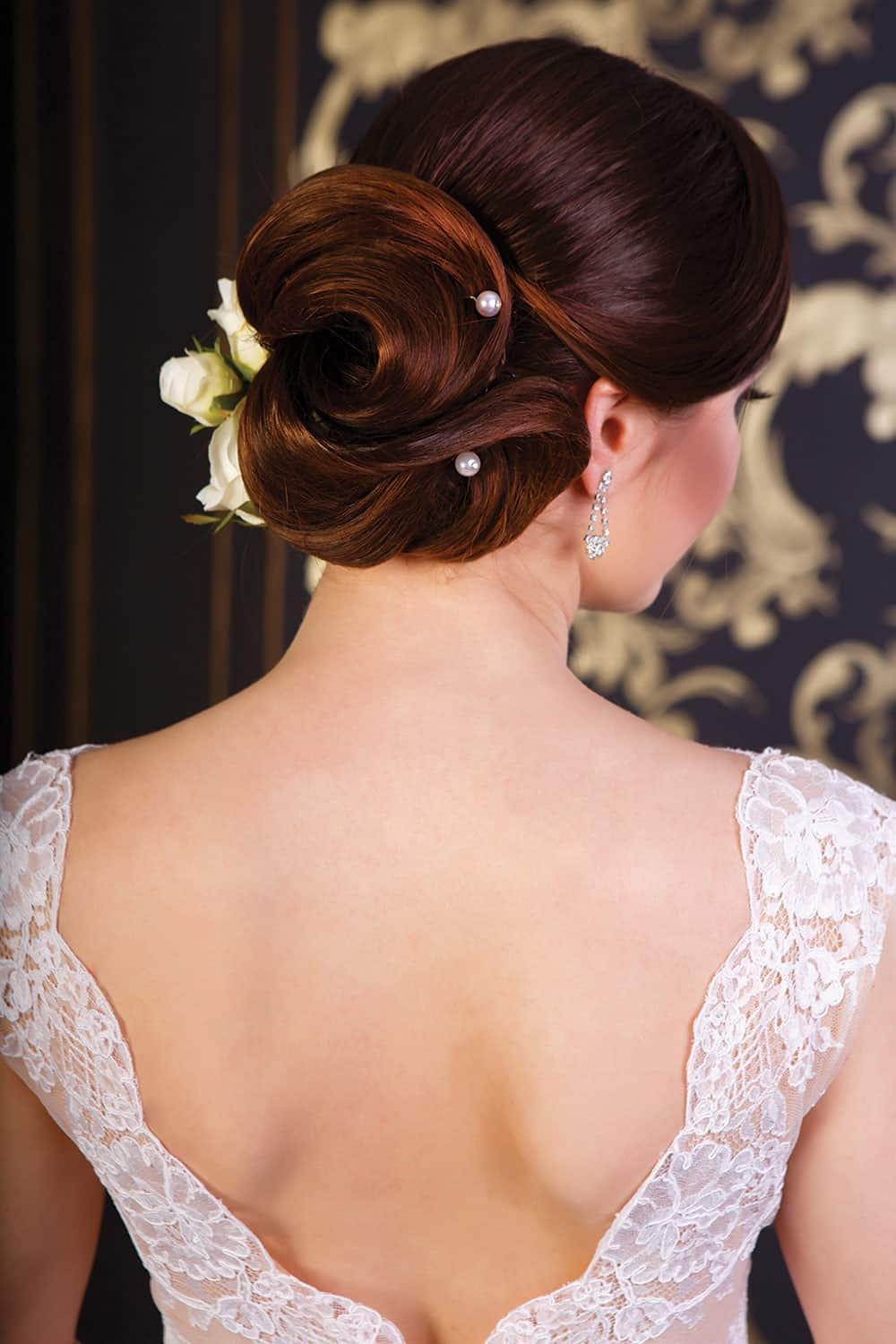 Spring Bridal hair up-do style with flower and woven pearls.