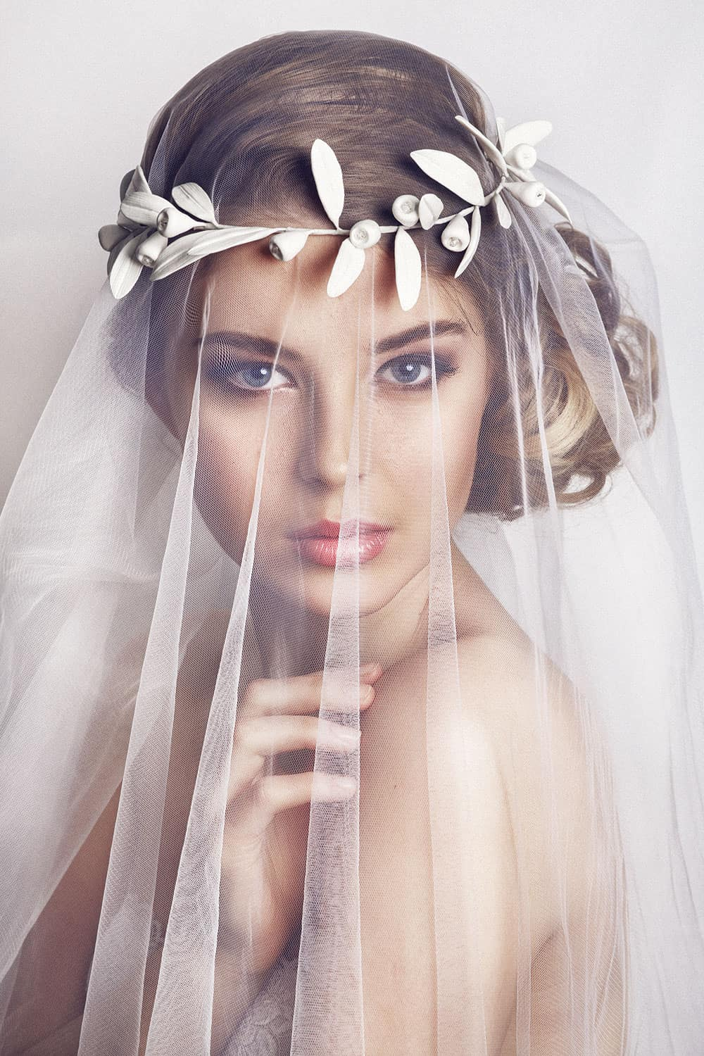 Spring bridal hair up-do style with veil and flowe crown.