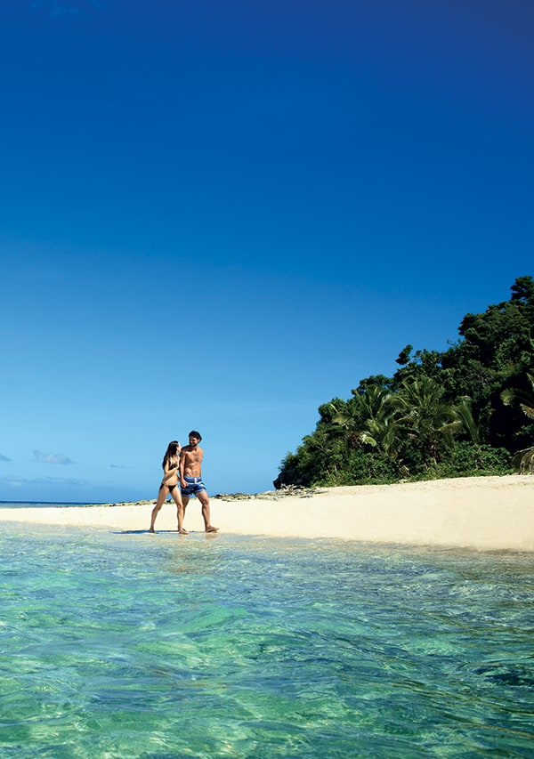 Couple walking along the beach in fiji on their honeymoon.