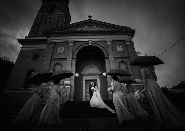 Bride and groom on the stairs of the church in black and white by Porfyri Photography