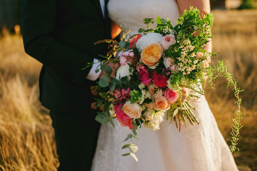 Cascading floral bouquet with Peach, coral and red roses and native ferns.