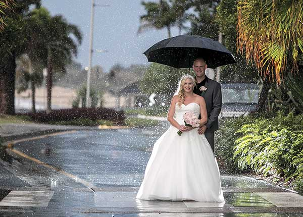 Bride and groom standing in the rain by Studio SW19