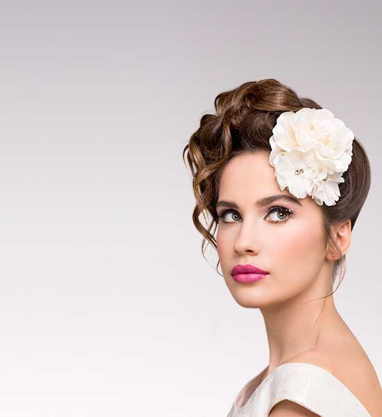 Bride with braided up-do accessorised with a flower & makeup by Two Makeup Chicks, wearing gown from Paddington Weddings.