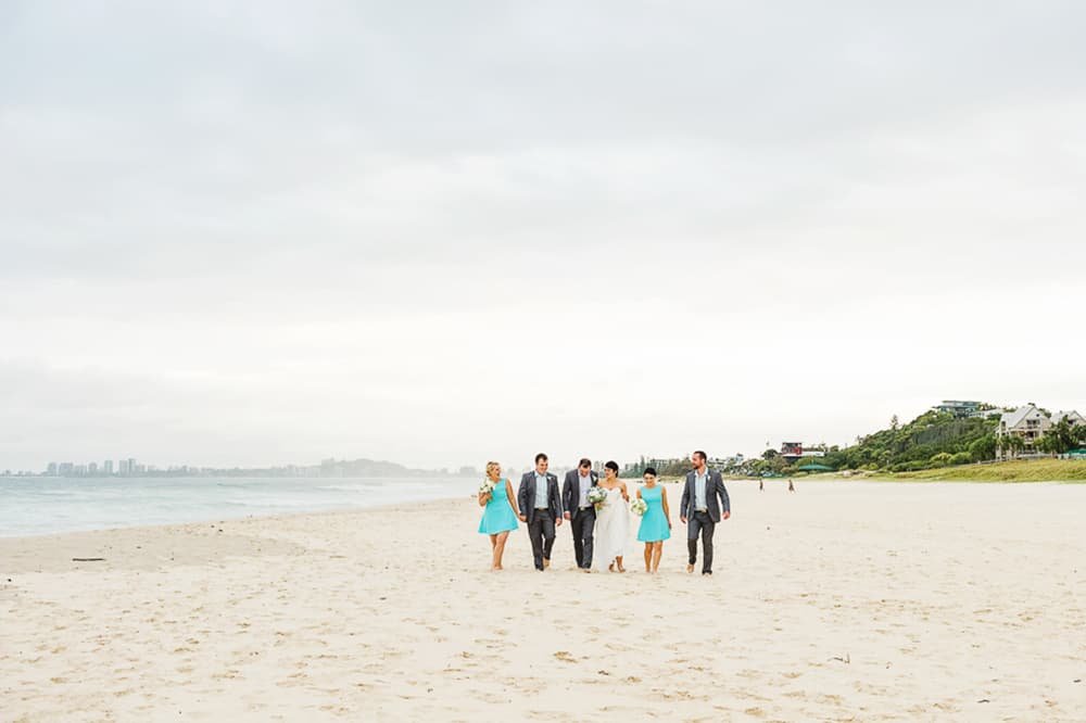Bridal party walking barefoot along the beach