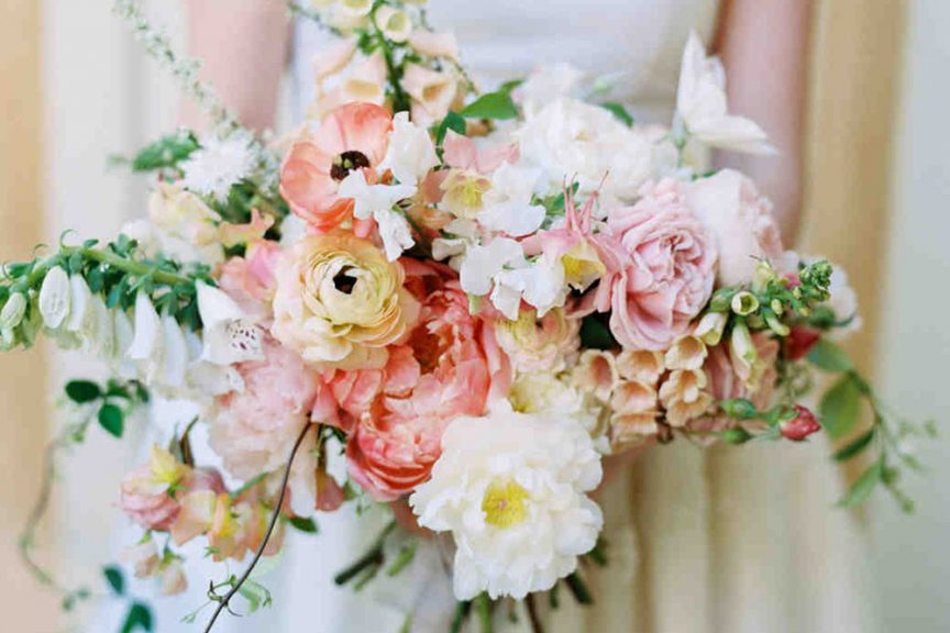 Cascading floral bouquet with peach, coral, green and white florals.