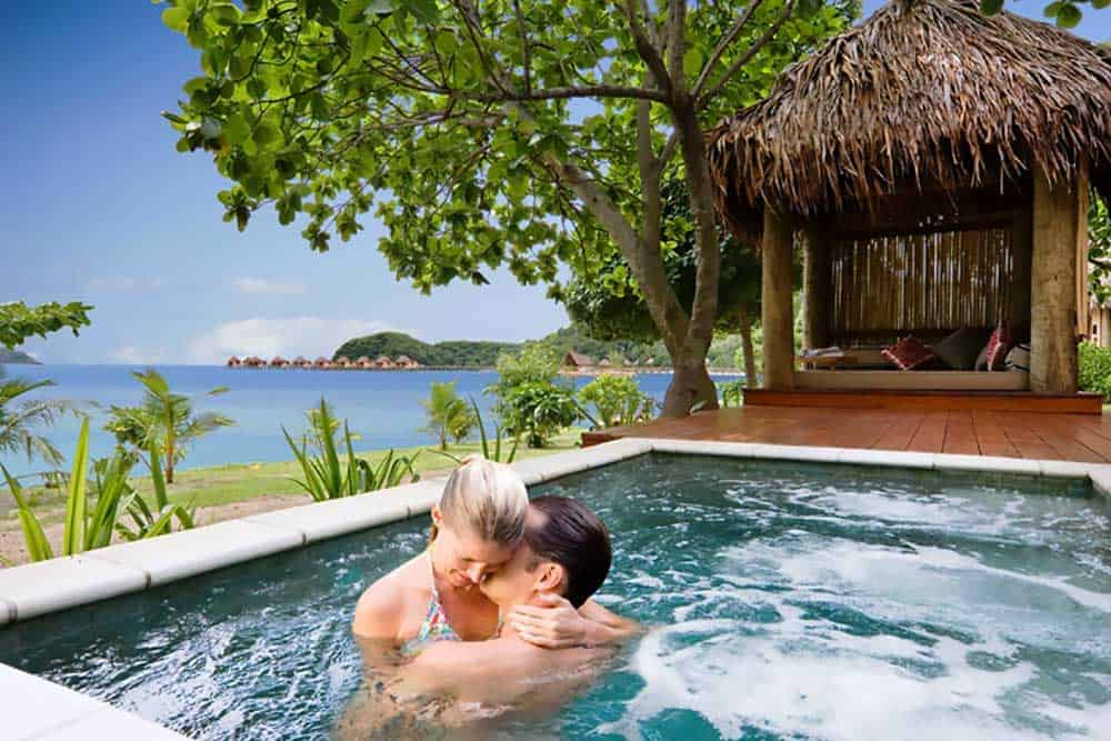 Honeymoon Fiji: a couple in the spa overlooking the turquoise waters of the islands.