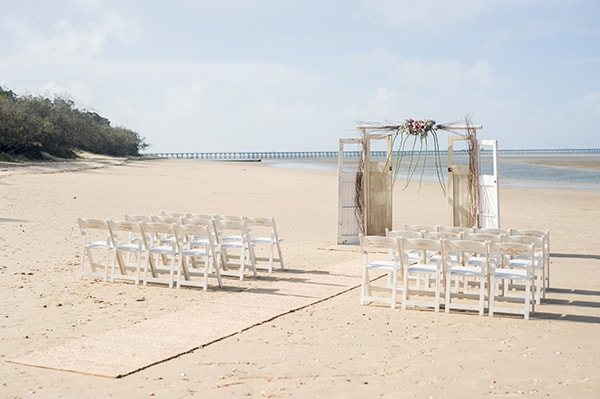 A beach wedding ceremony with driftwood and vintage door style arch.