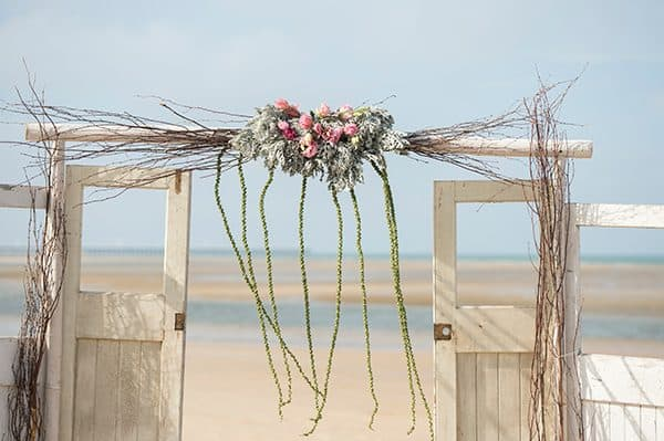 Vintage doors styled with natural florals for a beach wedding ceremony.