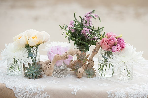 loosely arranged florals and driftwood for a beach ceremony