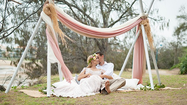 Bride and groom under a fabric tent after their beach ceremony.