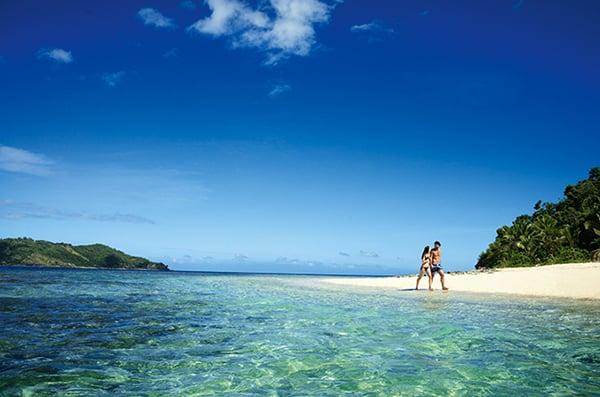 A couple walking along a Fijian beach on their honeymoon.