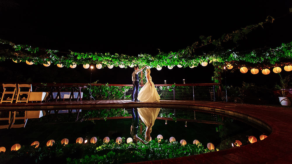 Bride and groom having their first dance outdoors by a lagoon.