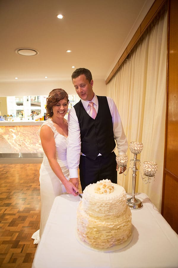 Bride and groom cutting the cake at their wedding reception in Redcliffe.
