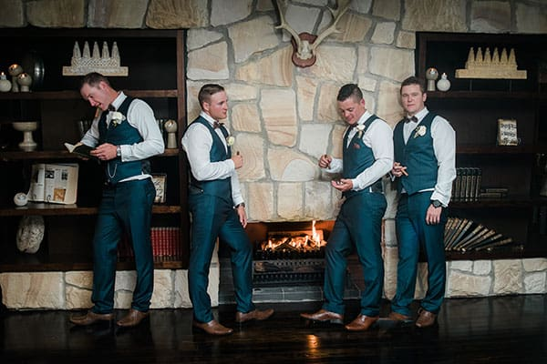 Groom and groomsmen by the fire at Mercure Clear Mountain Lodge.